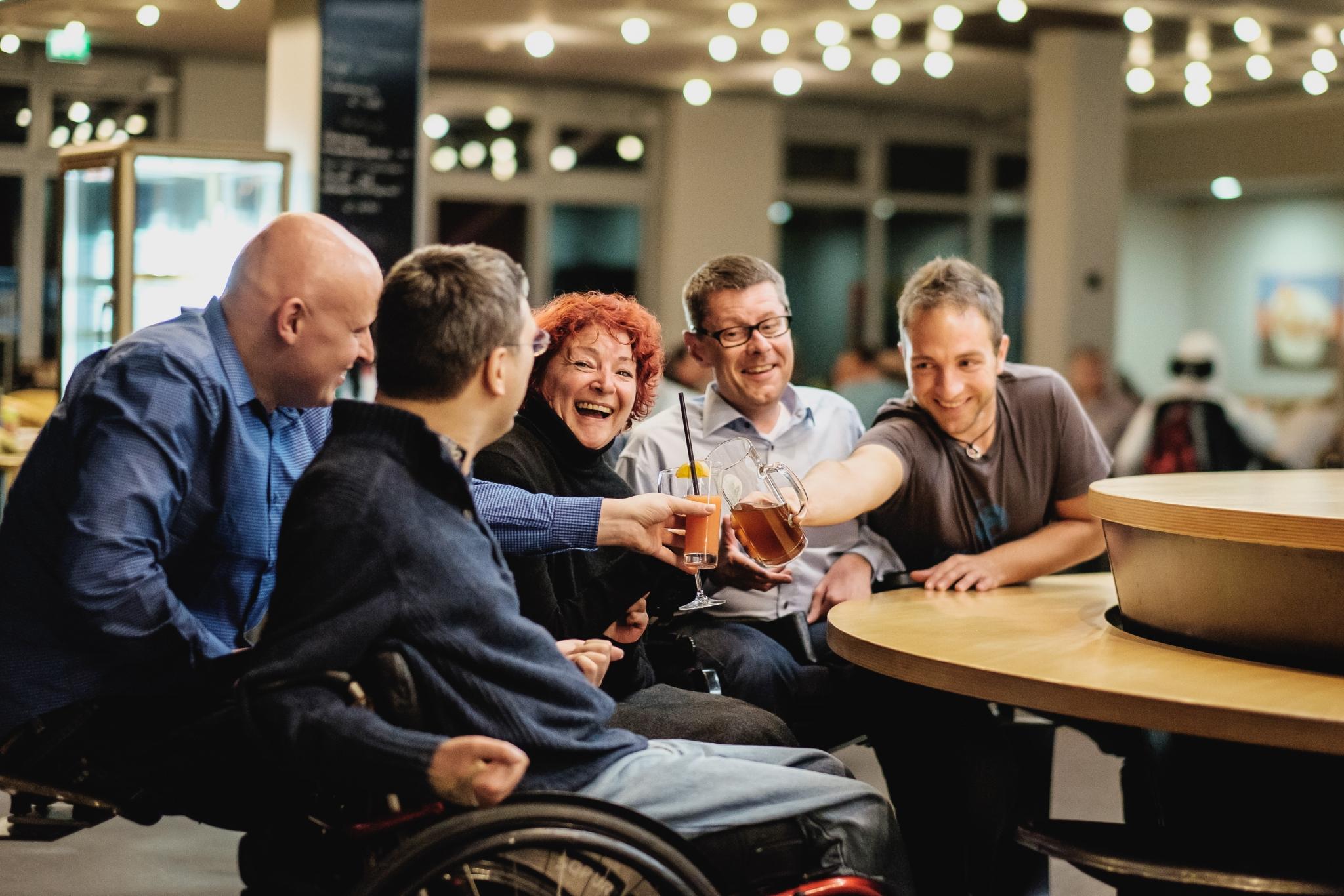 Eine Gruppe Menschen sitzt an einem Tisch und stößt mit Gläsern an.