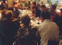 Auf dem Bild sind viele Menschen zu sehen, die an einem Tisch sitzen und sich entspannt unterhalten. Sie befinden sich in einem Café.